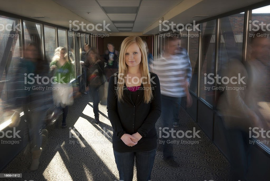 Young woman standing still in a moving crowd royalty-free stock photo