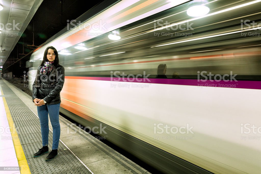 Young woman standing while Metro train passing thought a station stock photo