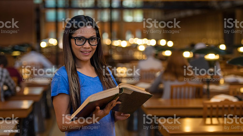 Young woman standing with book stock photo