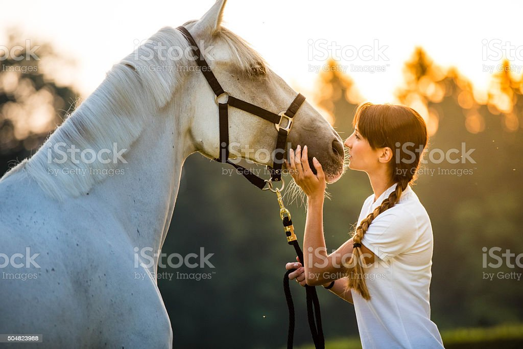 Young woman standing with horse stock photo