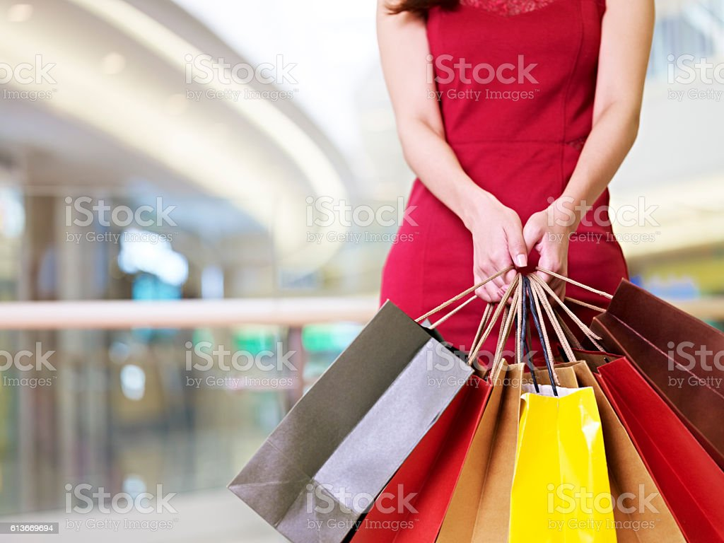 young woman standing with shopping bags in hands stock photo