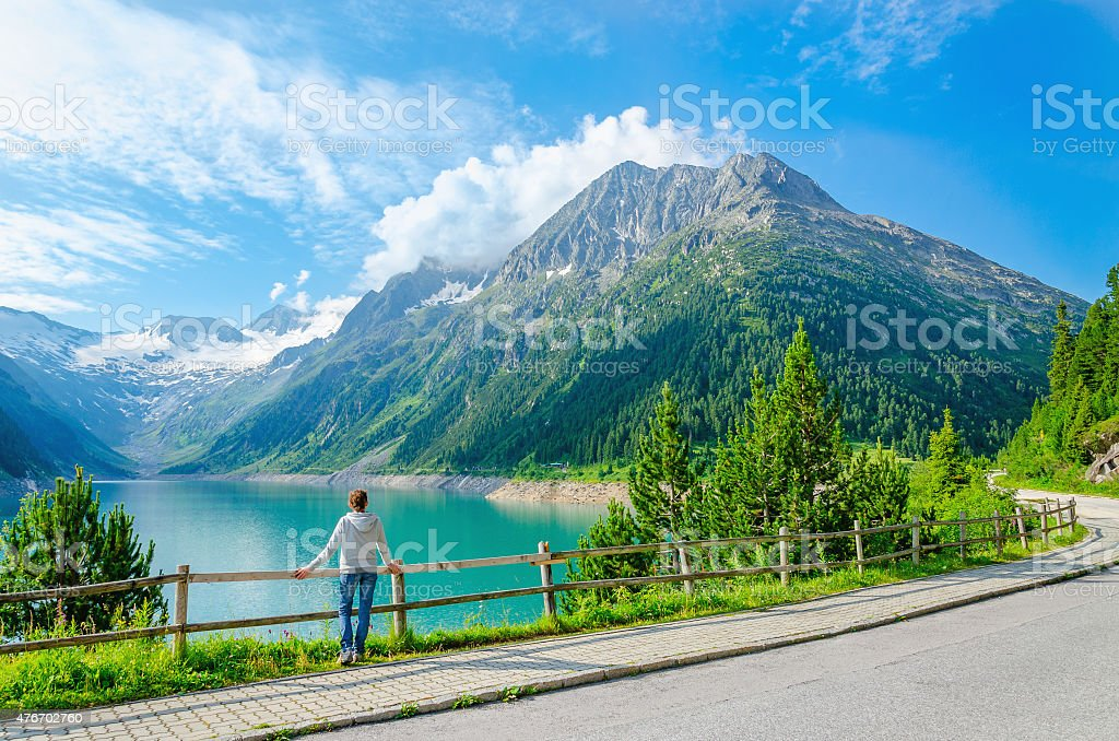 young woman stands by mountain lake , Austria stock photo
