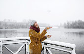 Young woman stands near a frozen lake.