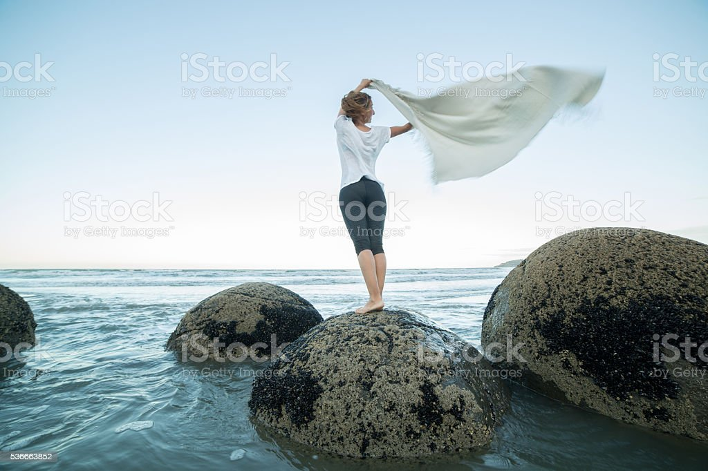 Young woman stands on boulder, holds blanket in the air stock photo