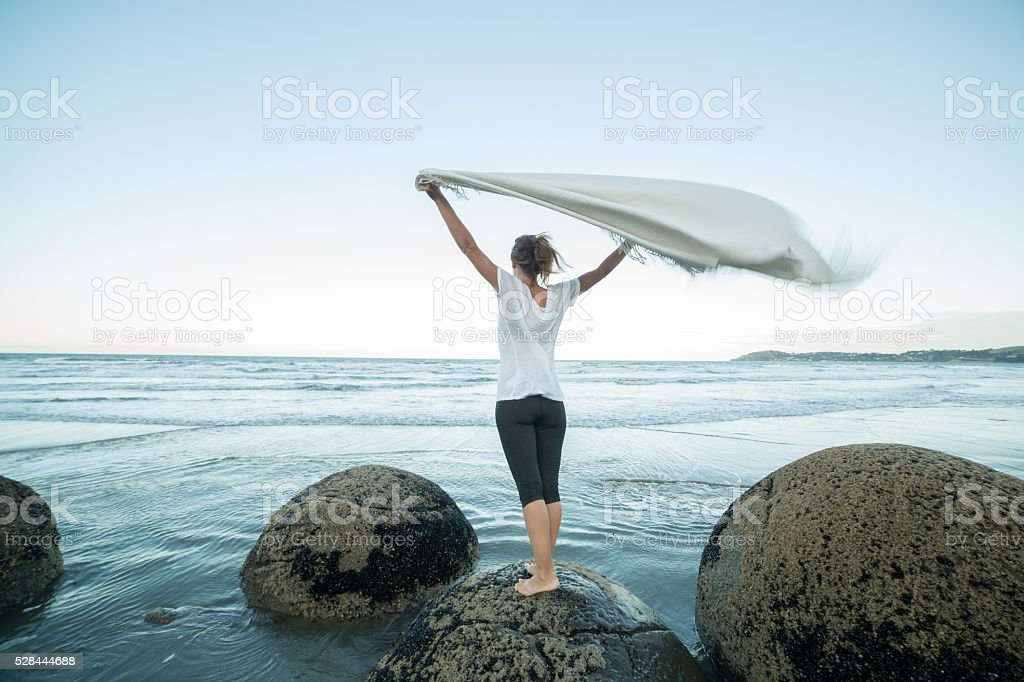 Young woman stands on boulder, pulls out blanket in air stock photo