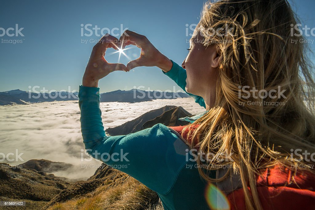 Young woman stands on mountain peak, frames sunbeam stock photo