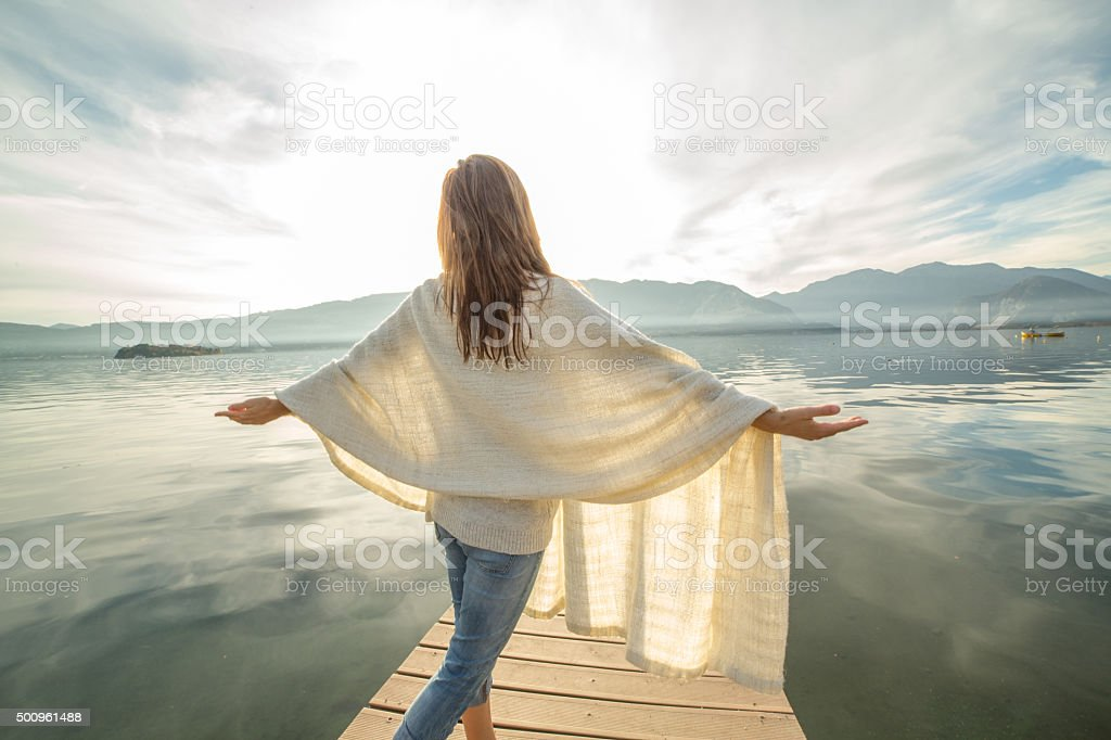 Young woman stands on pier arms outstretched, relaxes stock photo