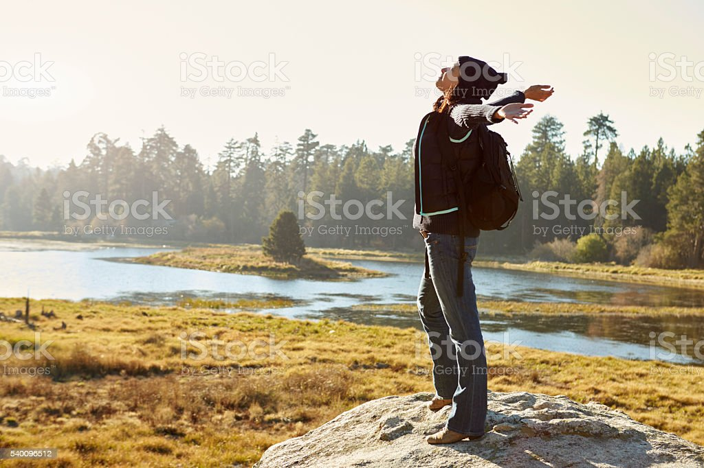 Young woman stands on rock in countryside, arms outstretched stock photo