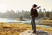Young woman stands on rock in countryside, arms outstretched