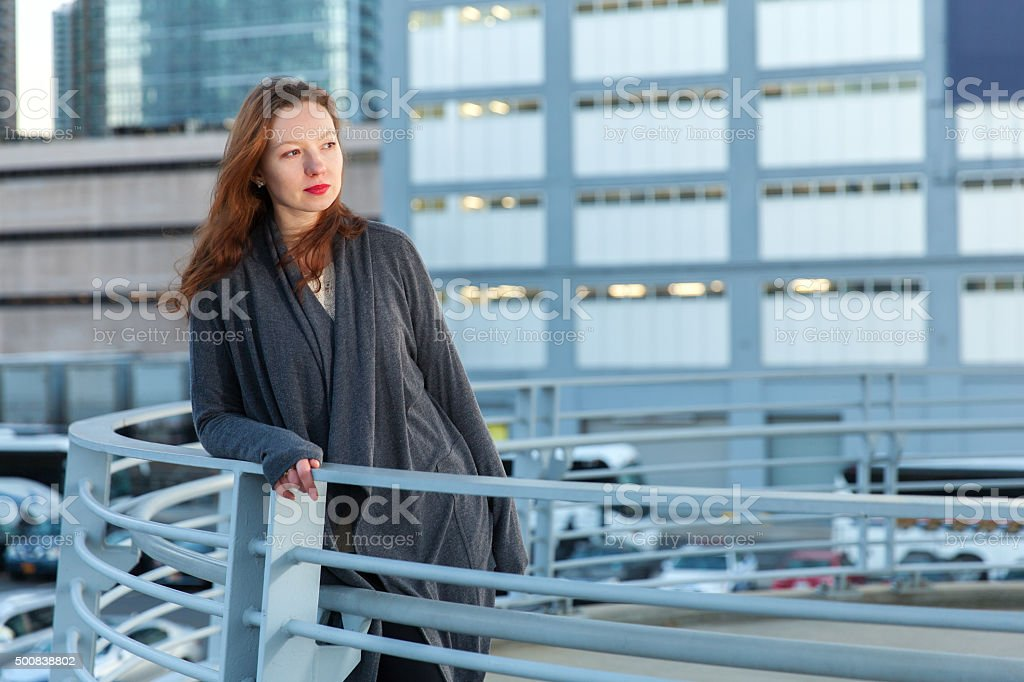 Young woman stands on round balcony leaning at handrails stock photo
