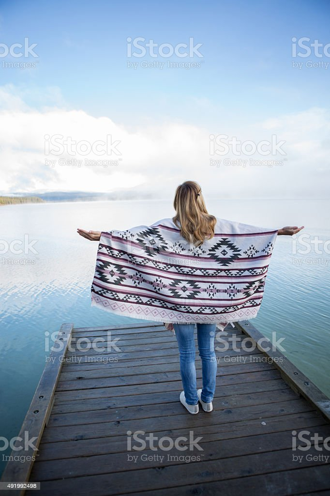 Young woman stands on wooden pier arms outstretched for freedom stock photo