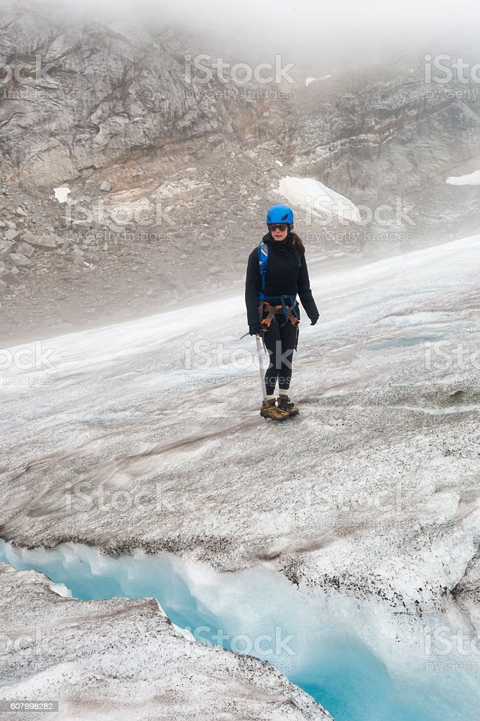 Young woman stares at crevasse stock photo