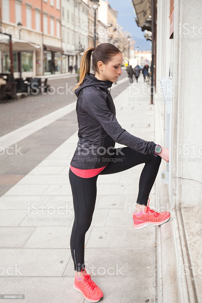 Young woman Stopping at the ATM while Jogging stock photo