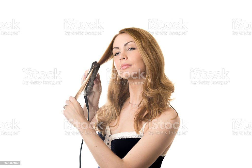 Young woman straightening curly hair stock photo