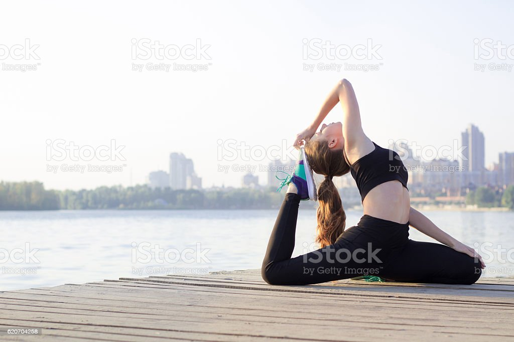 Young woman stretches at triangle pose during training workout outdoor stock photo
