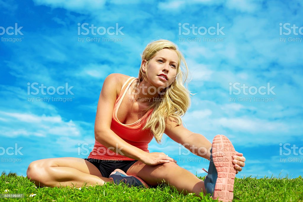 Young Woman Stretching At Park stock photo