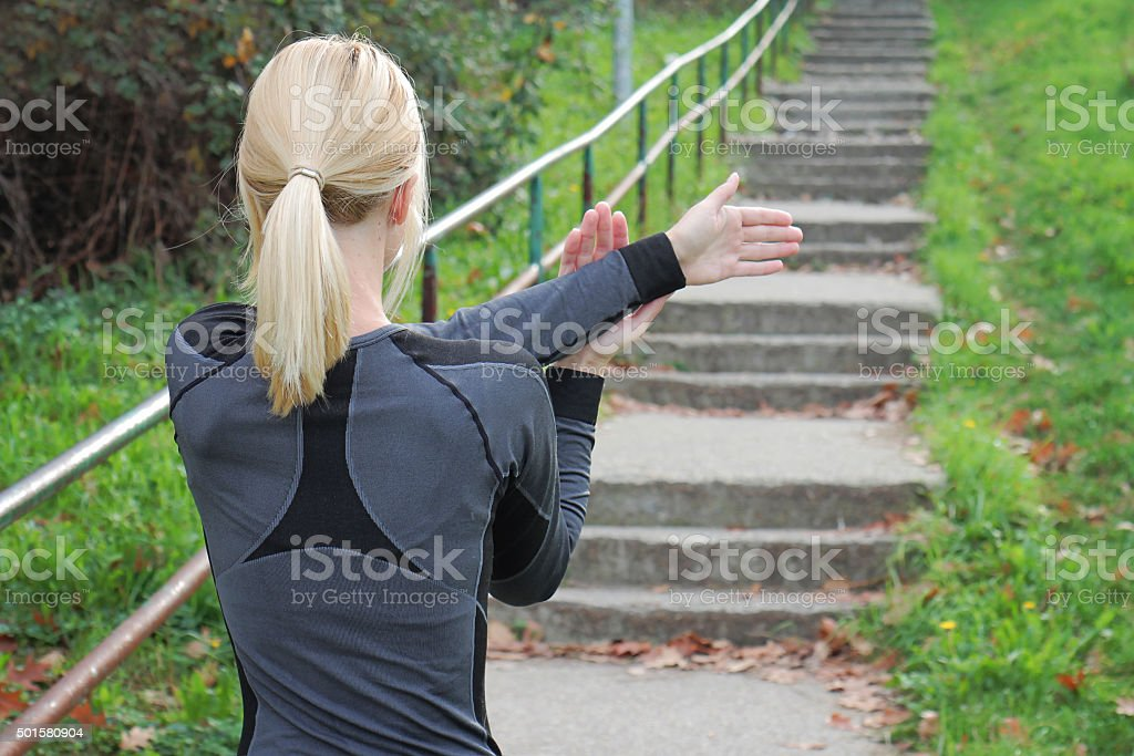 Young woman stretching before running stairs workout outdoors stock photo