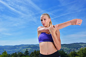 Young woman stretching her arms up while exercising on mountain