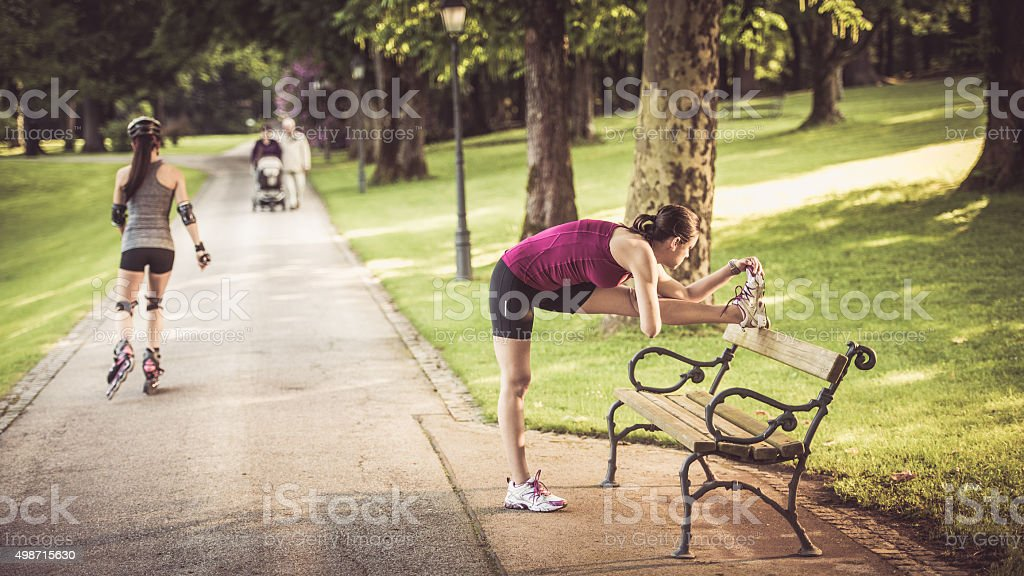 Young woman stretching her leg on a park bench stock photo