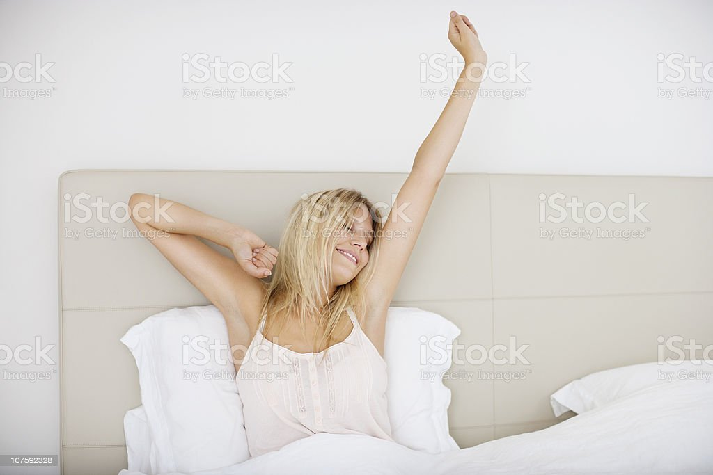 Young woman stretching in bed royalty-free stock photo