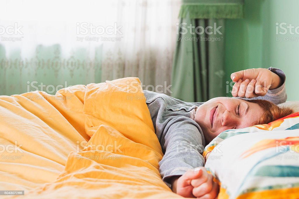 Young woman stretching in bed stock photo