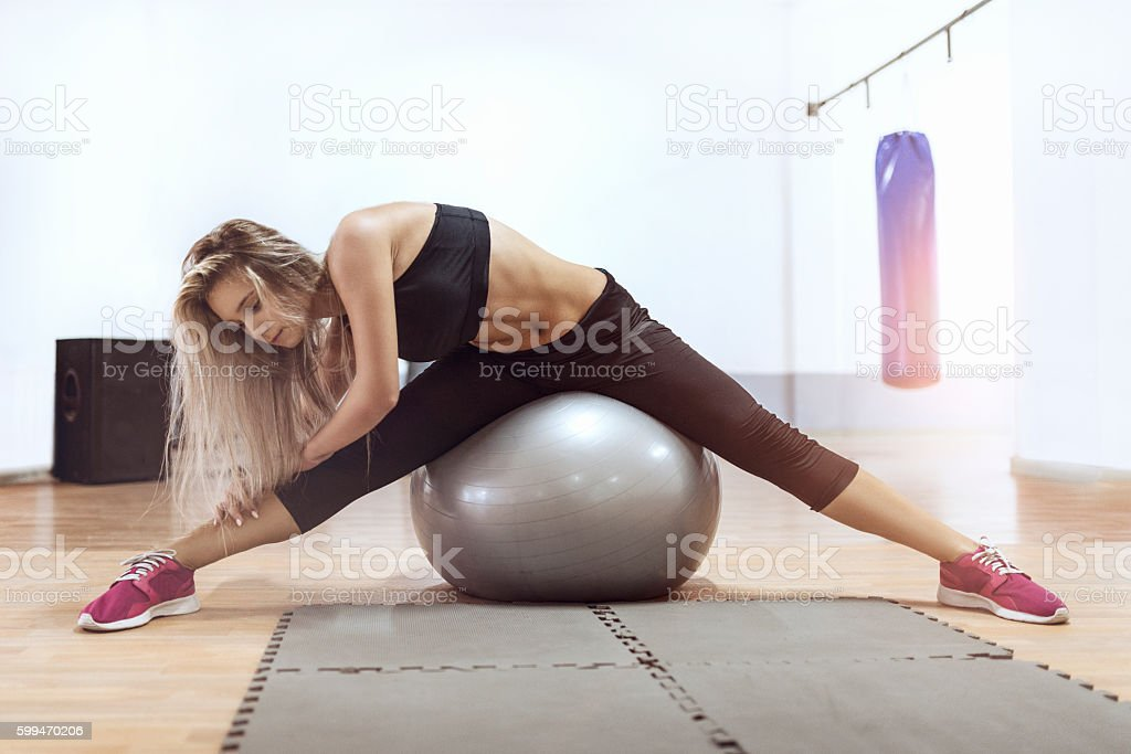 Young Woman Stretching in Gym Training with Exercise Ball stock photo