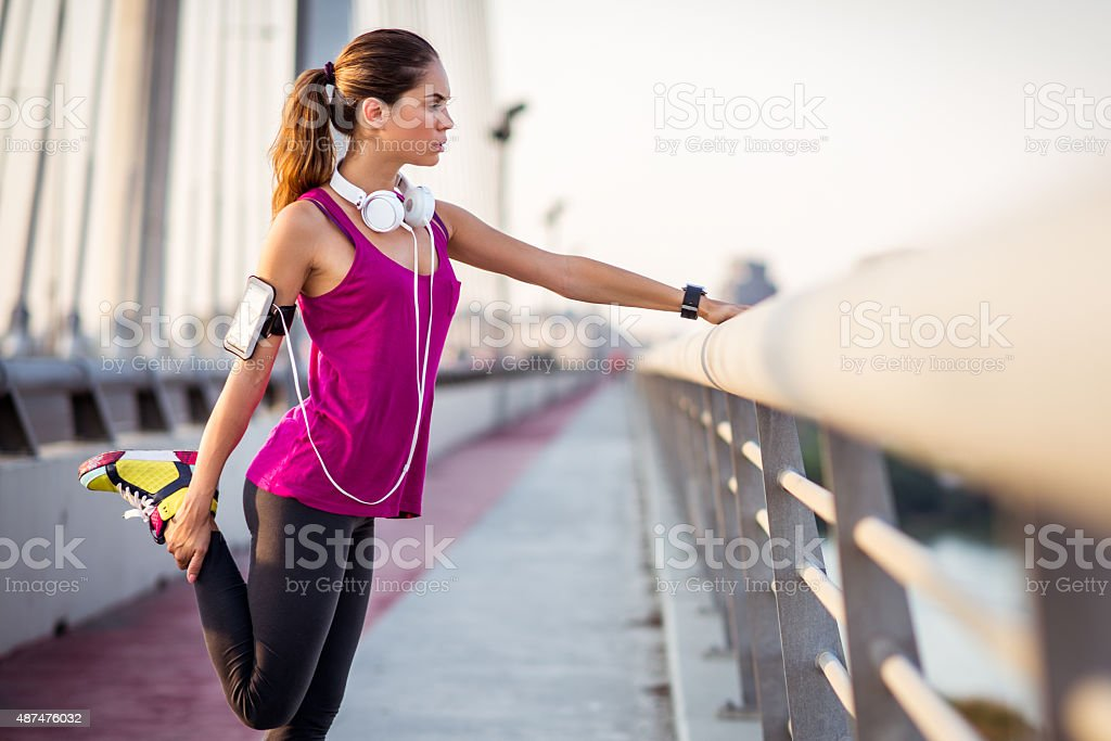 Young woman stretching leg after running stock photo