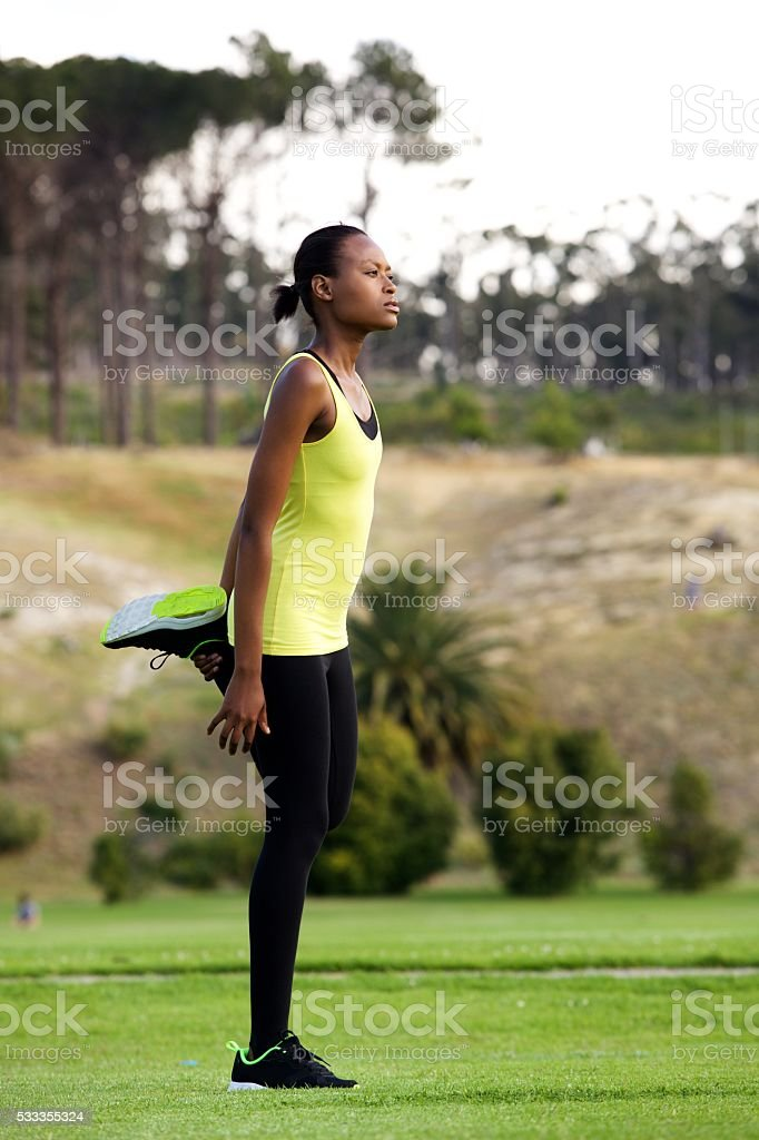 Young woman stretching leg muscles outdoors stock photo