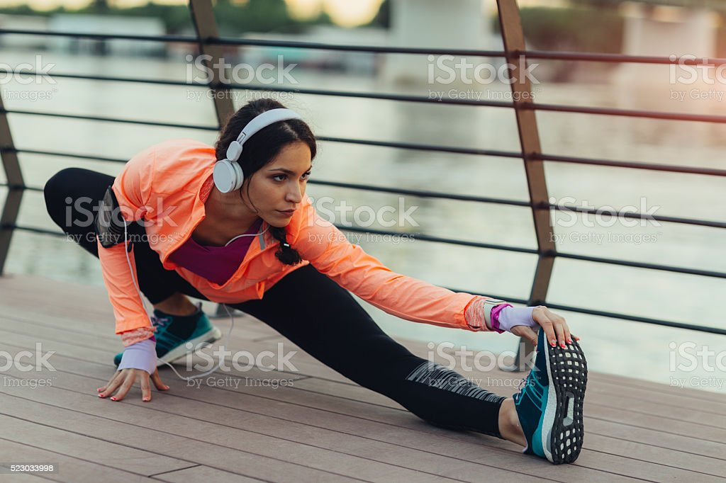 Young Woman Stretching Near River. stock photo