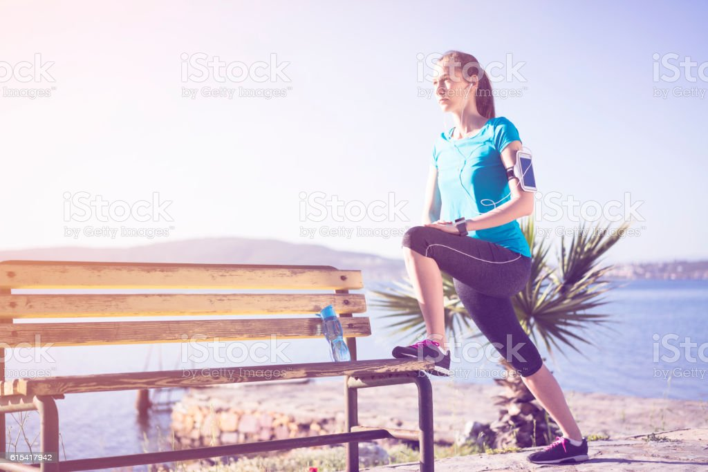Young woman stretching on a bench stock photo