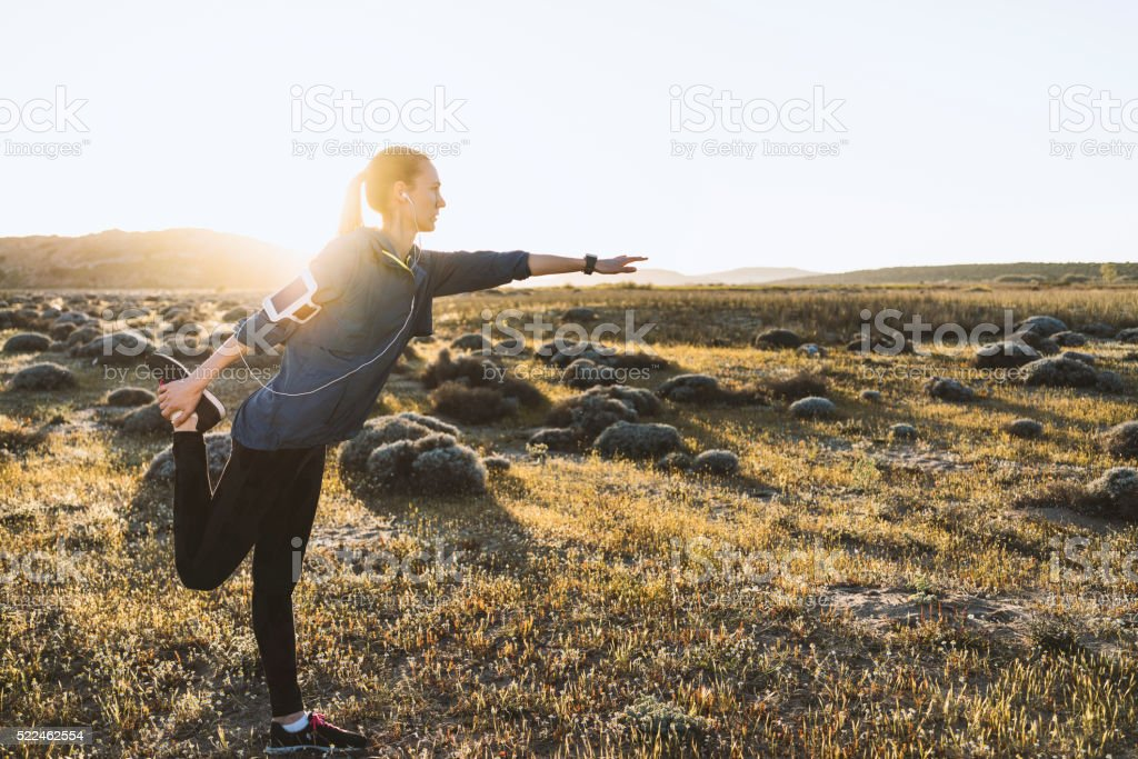 Young woman stretching on a sunny day stock photo