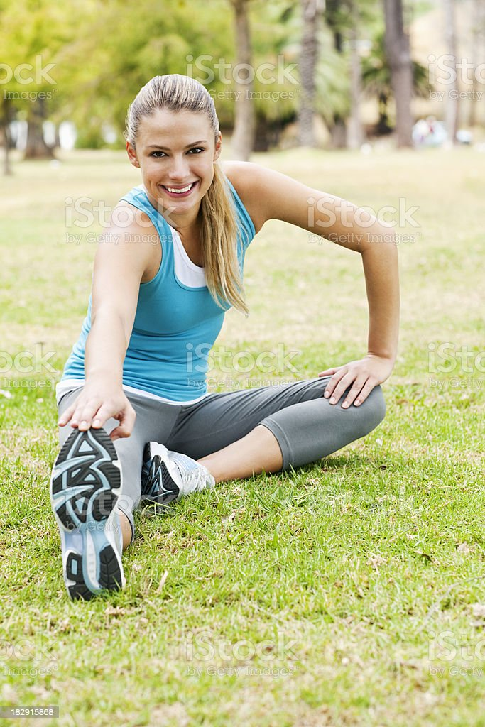 Young Woman Stretching on the Park Ground royalty-free stock photo