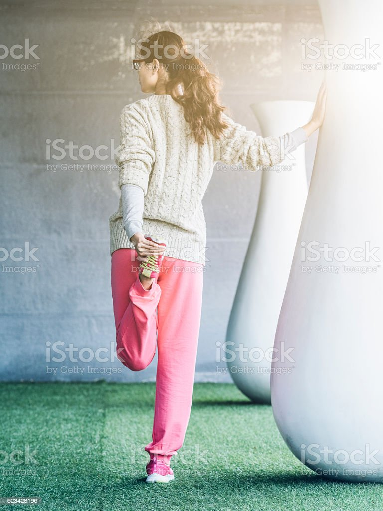 young woman stretching outdoor stock photo