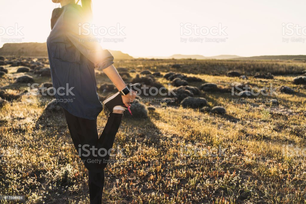 Young woman stretching outdoors stock photo