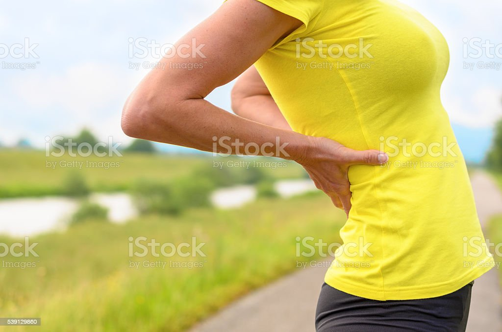 Young woman stretching with her hands to her back stock photo