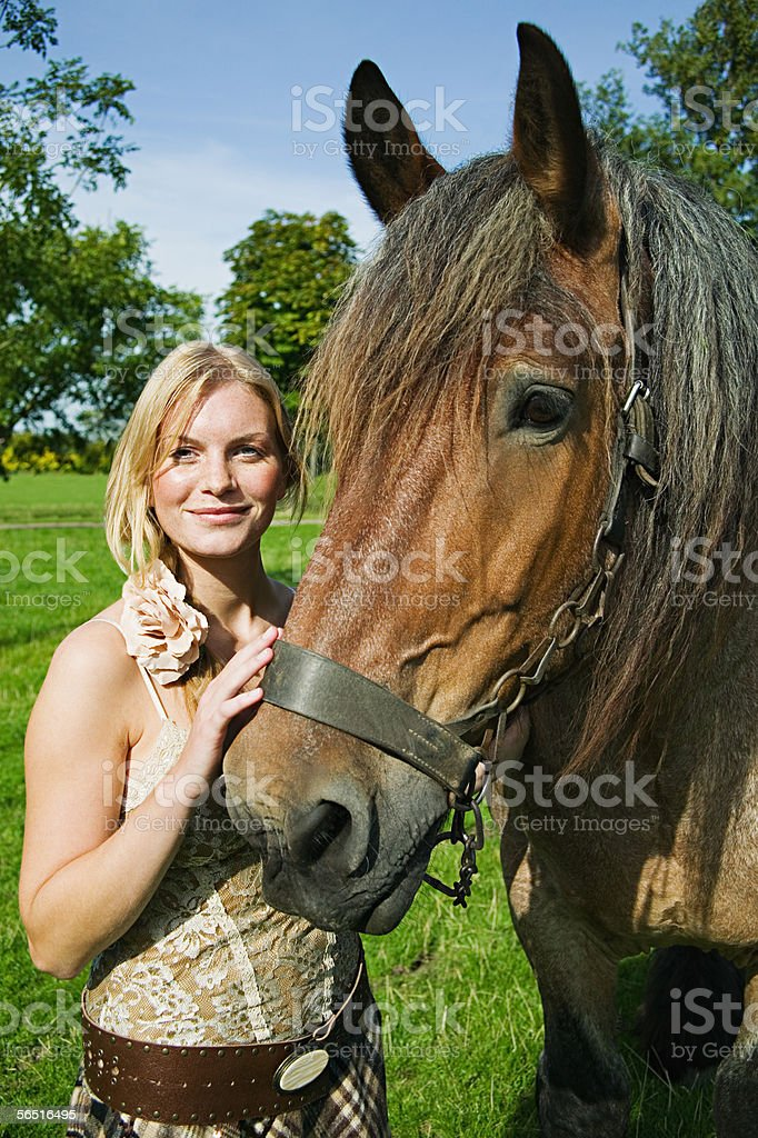 Young woman stroking a horse stock photo