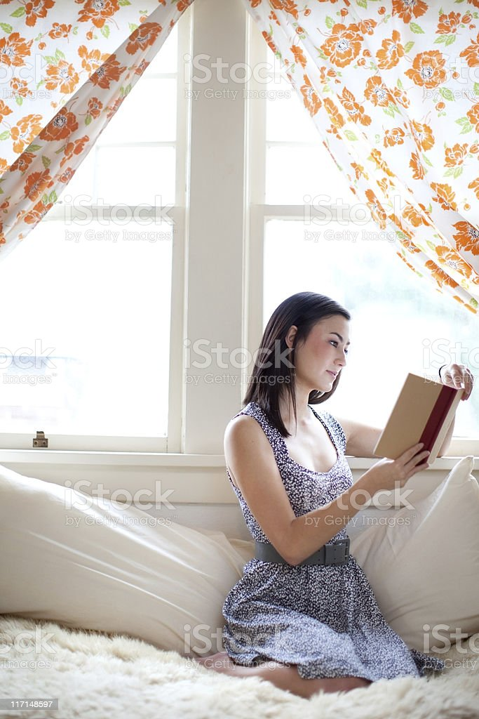 Young Woman Student Reading By Window stock photo
