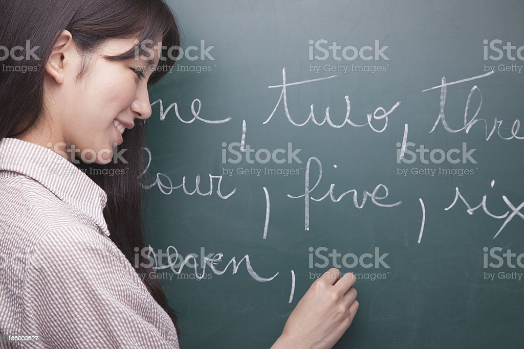 Young woman student writing English numbers on blackboard stock photo