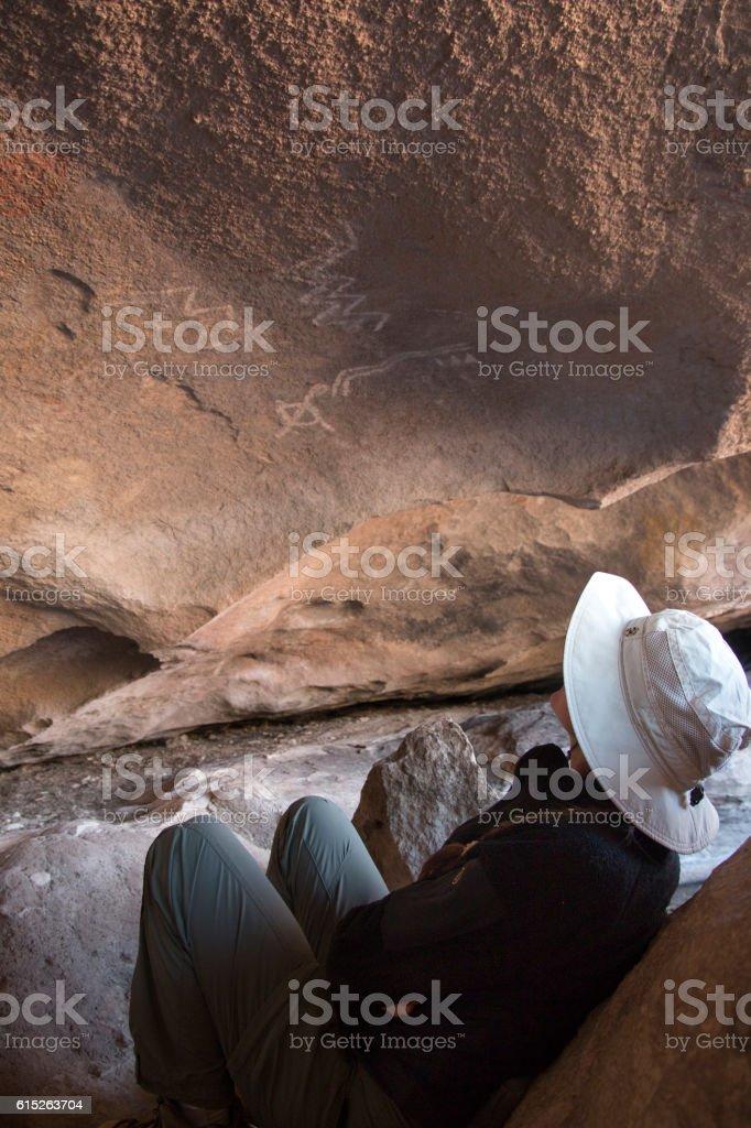Young woman studies Native American rock art Hueco Tanks Texas stock photo
