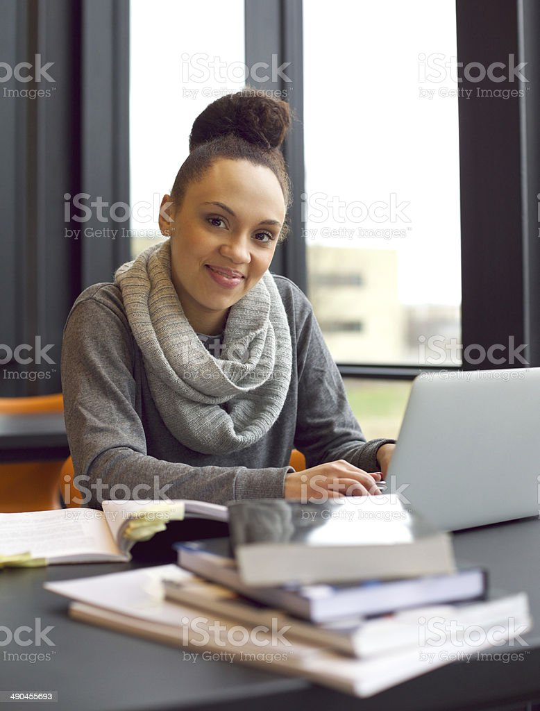Young woman studying at a desk using books and laptop stock photo