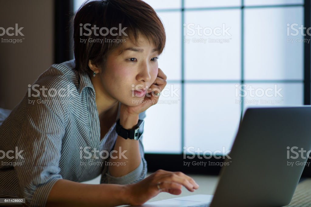 Young woman studying at home at night stock photo