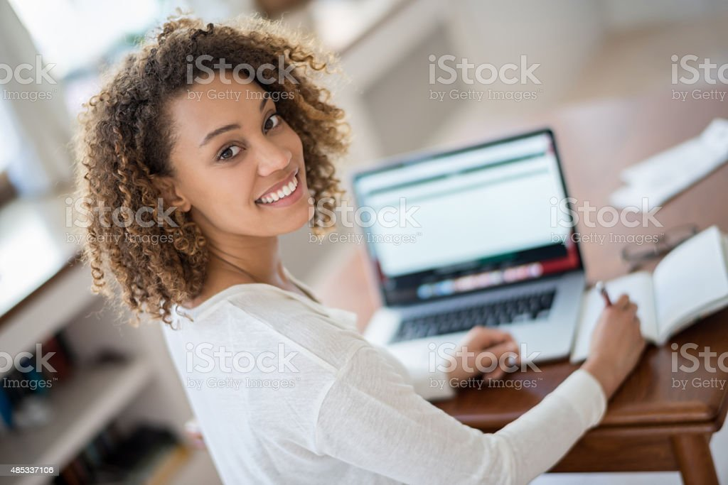 Young woman studying at home stock photo