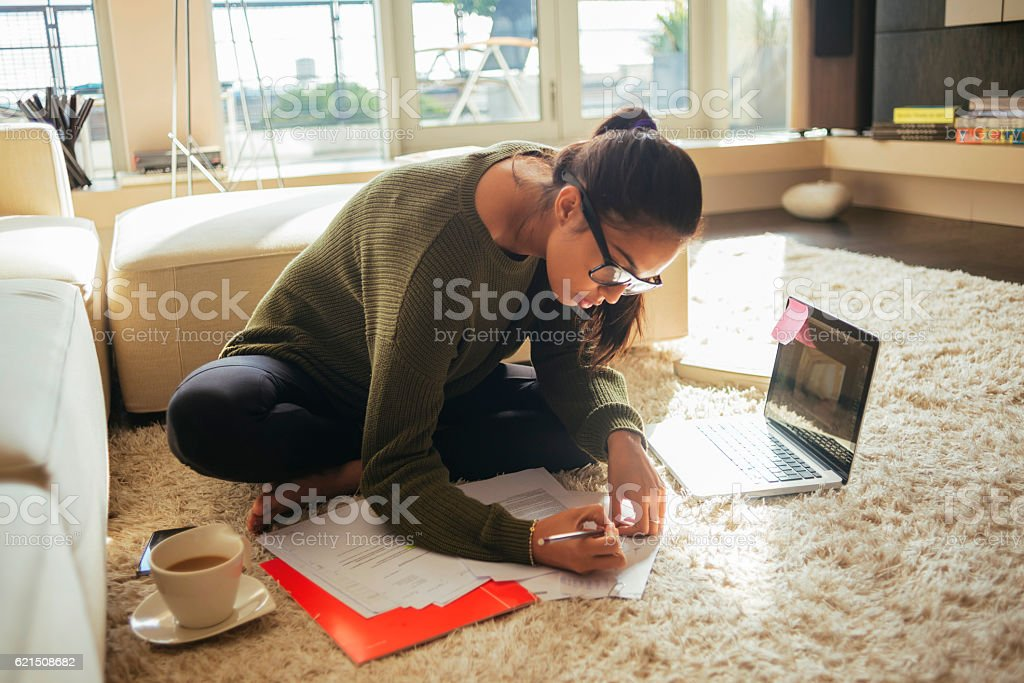 young woman studying in her living room stock photo