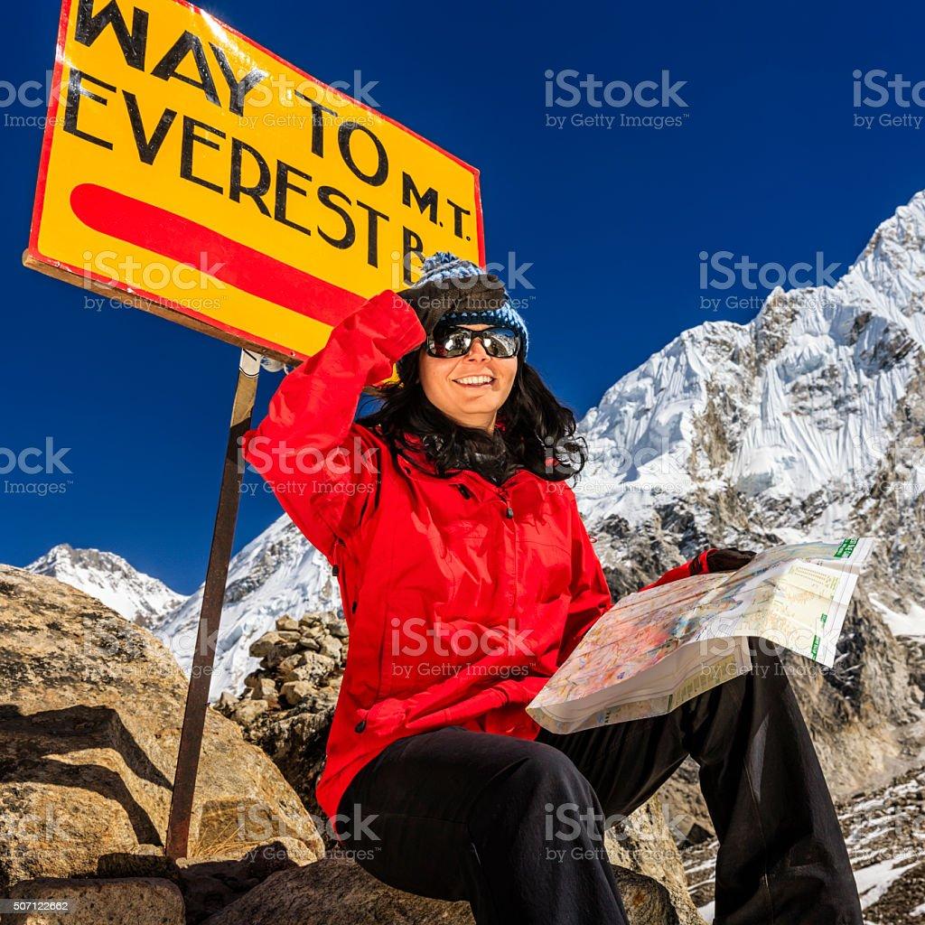 Young woman studying map next to signpost, Nepali Himalaya stock photo