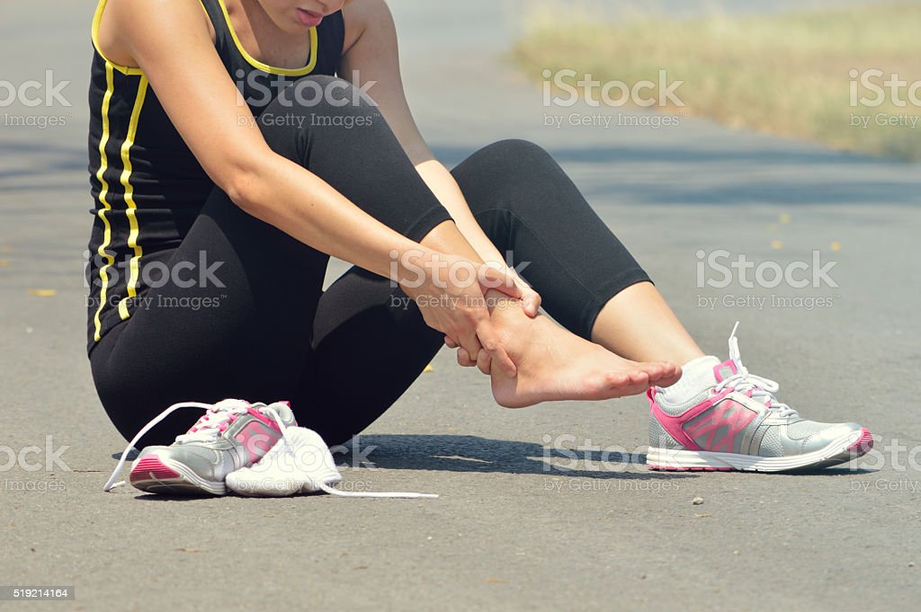 Young woman suffering from an ankle injury while exercising and stock photo