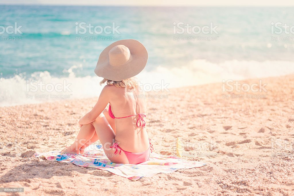 Young woman sunbathing at the sea shore stock photo