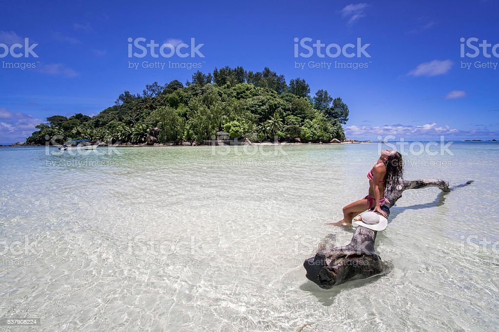 Young woman sunbathing during summer day on Moyenne island. stock photo