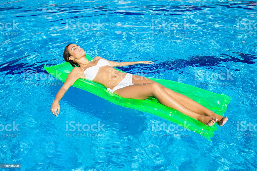 Young woman sunbathing in a swimming pool stock photo