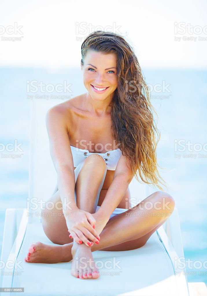 Young woman sunbathing on a beach stock photo