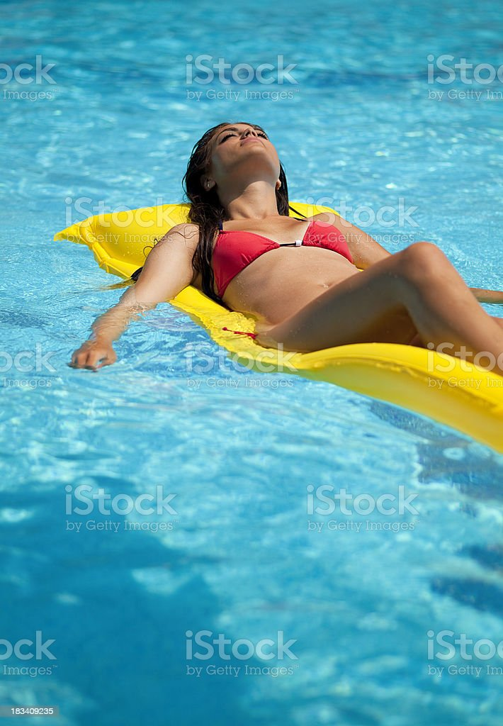 Young woman sunbathing on air bed in swimming pool royalty-free stock photo